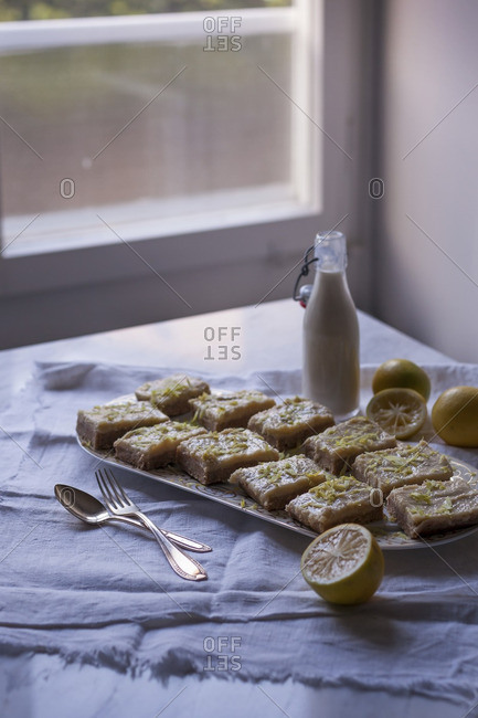 Raw coconut and lemon squares for dessert on a serving plate, sprinkled with lemon zest