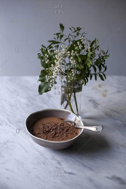 Chocolate mousse sprinkled with grated dark chocolate in a small bowl on white marble table