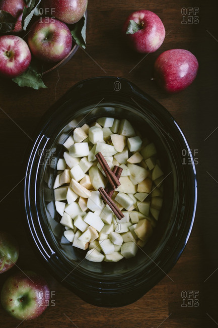 Sliced and peeled apples are placed in the bowl of a slow cooker - photographed from the top view.