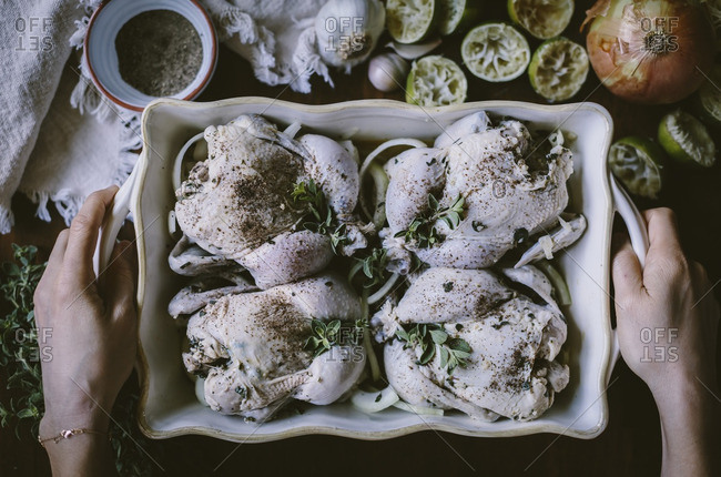 4 seasoned game hens are placed in a casserole pan are about to be placed in the oven.