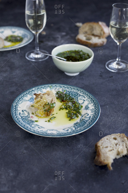 Italian Style Salsa Verde served with bread and white wine. Photographed from front view on a dark grey background.