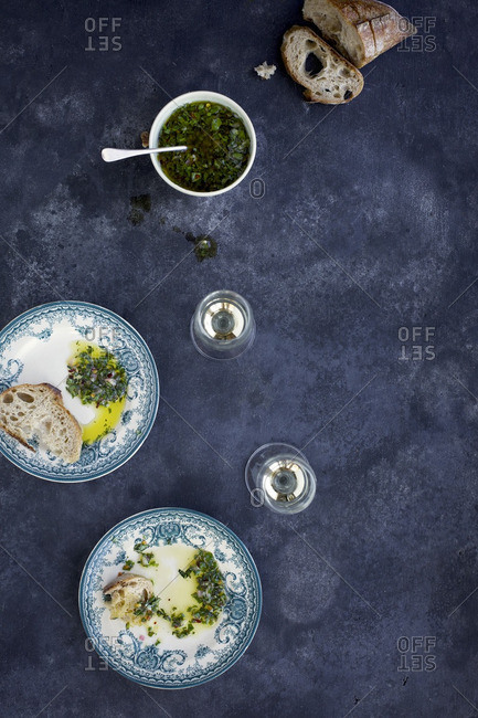 Italian Style Salsa Verde served with bread and white wine. Photographed from top view on a dark grey background.