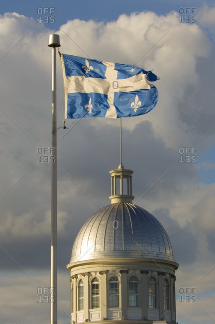 Flag of province of Quebec flies over the dome of Bonssecour Market in old Montreal, Montreal, Quebec, Canada.