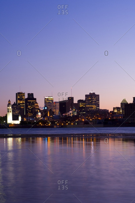 Evening view of skyline with old Montreal in foreground, across St. Lawrence River from Ile Notre-Dame, Montreal, Quebec, Canada.