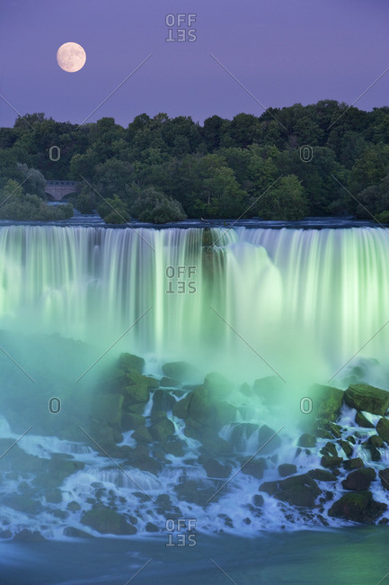 The American Falls with Full moon at dusk lit with lights photographed from Niagara Falls, Ontario, Canada.
