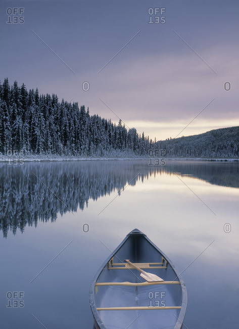 Canoe on Winchell Lake after first snowfall, Alberta, Canada.