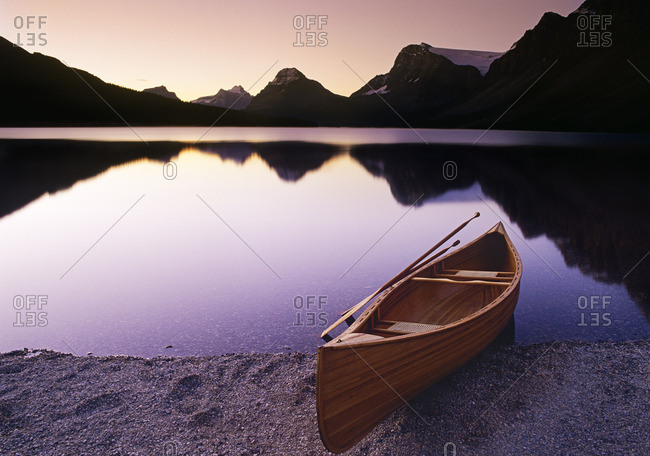 Canoe on the shore of Bow lake at dawn, Banff National Park, Alberta, Canada.