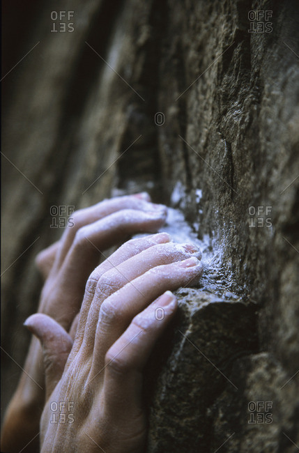 the chalked up hands of a determined climber hanging on to a ledge, Skaha, Penticton, British Columbia, Canada.