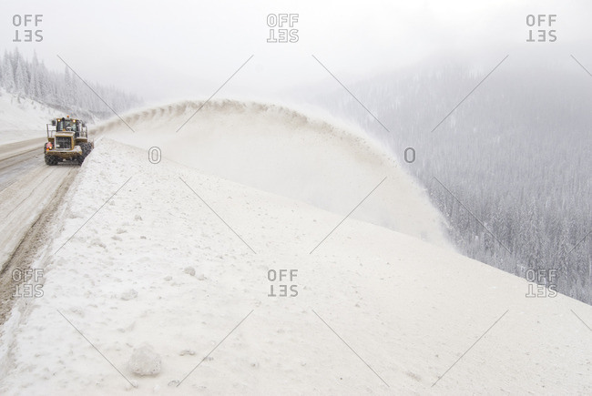 Highway maintenance crew clears road with large snow plume over snow bank, Salmo-Creston Pass, Kootenay Pass, Crowsnest highway, British Columbia, Canada.