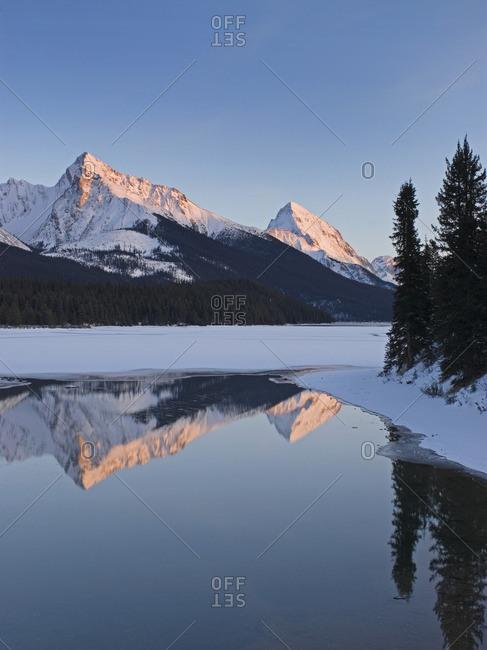 The Rocky Mountains form the backdrop for Maligned Lake, near Jasper, Alberta, Canada.