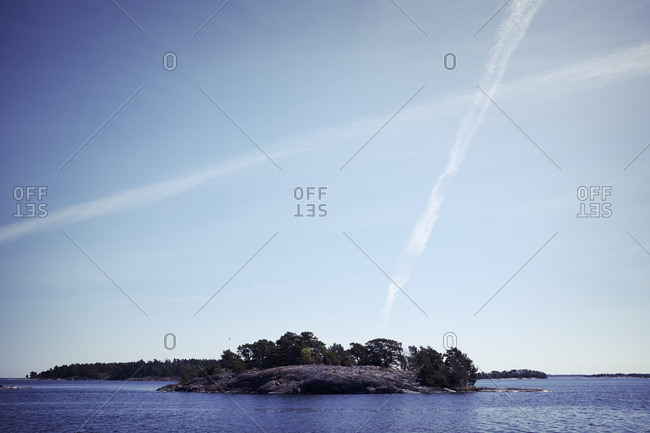 Vapor trail on sky above small island