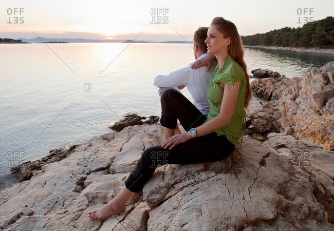 Couple watching sun set at rocky beach