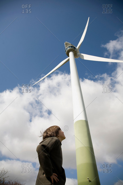 Boy looking up at wind turbine