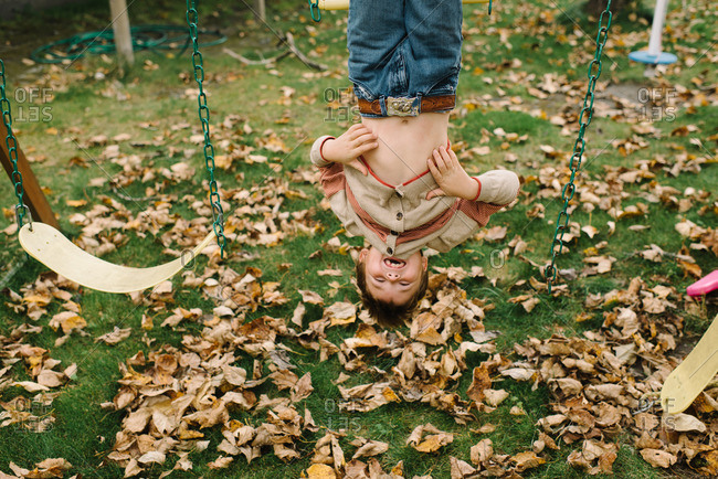 Boy hanging upside down from a swing set in his backyard