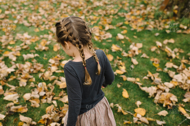 Girl walking through dry autumn leaves