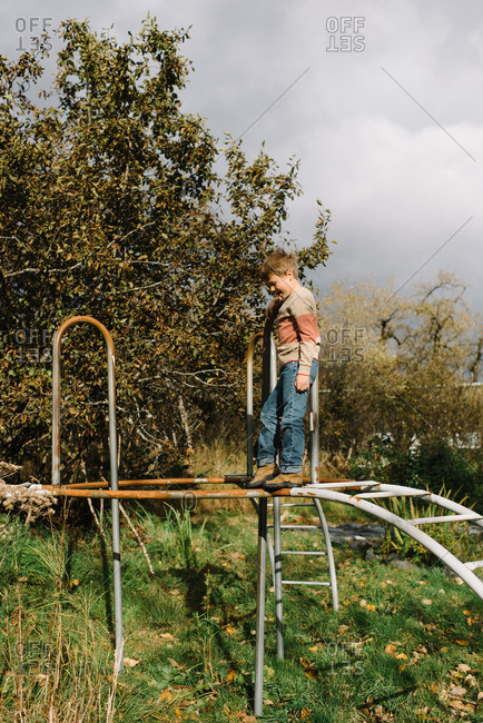 Boy standing on top of a play structure