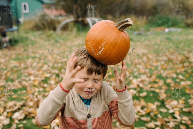 Boy trying to balance a pumpkin on his head