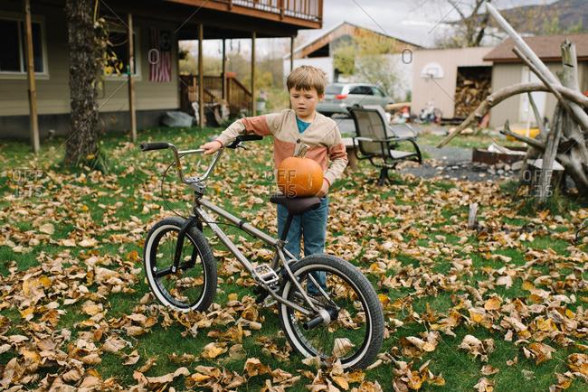 Boy balancing a pumpkin on his bicycle seat
