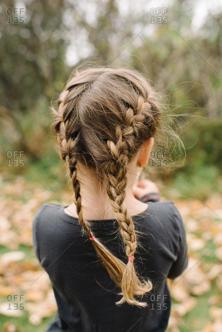 Girl with braided hair standing outside on an autumn day