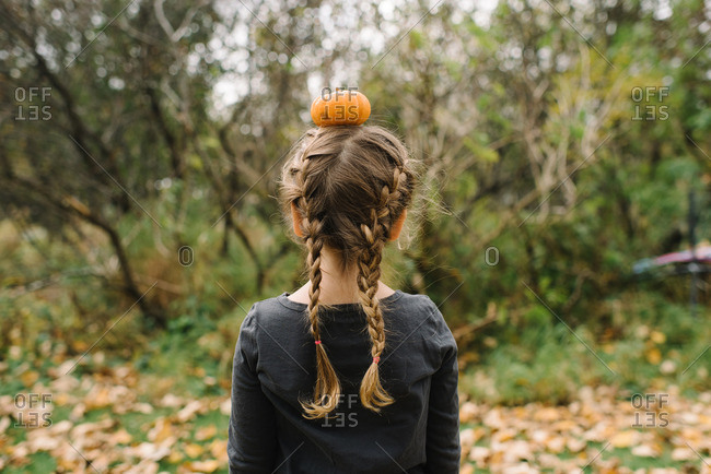 Girl with braided hair balancing a small pumpkin on her head
