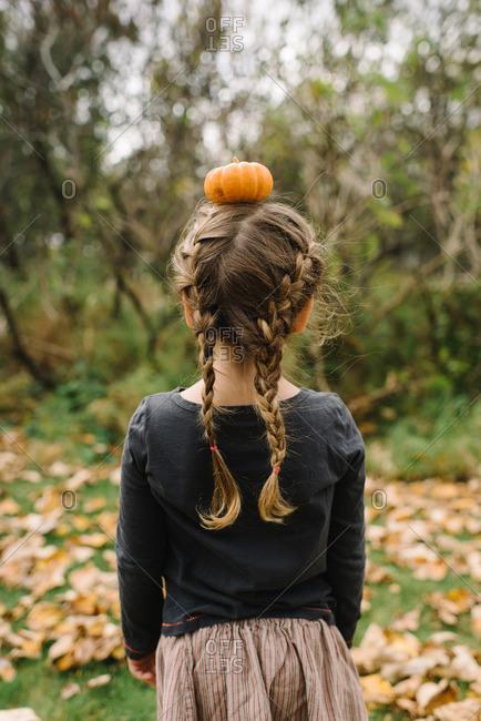 Girl with braided hair balancing a miniature pumpkin on her head