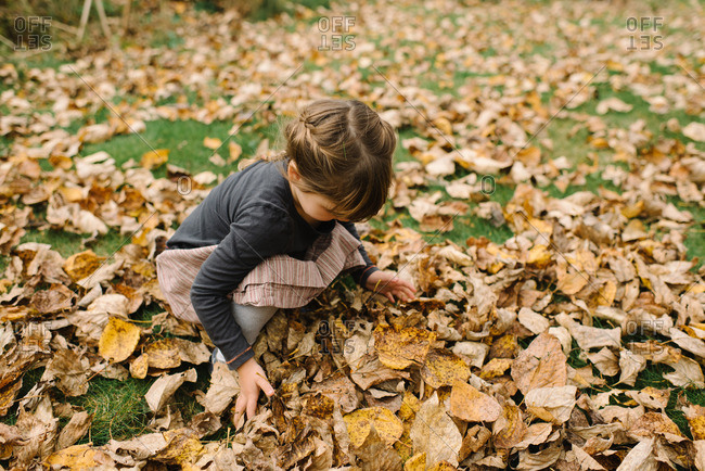 Girl with braided hair playing in the leaves on an autumn day