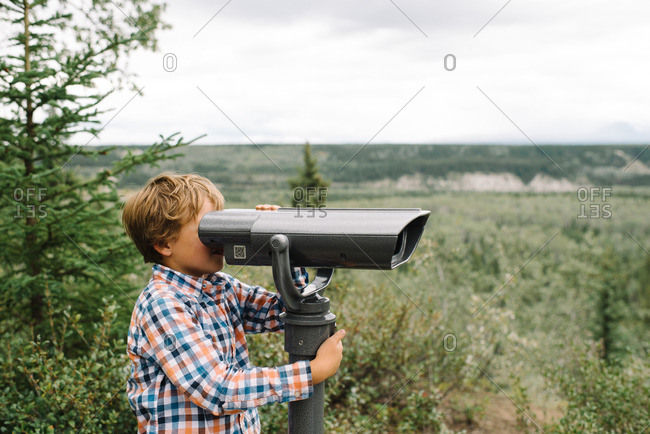 Boy looking through a viewing scope on the edge of a forest