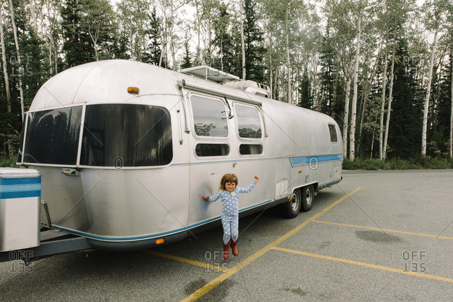 Girl jumping up alongside a silver camper trailer parked in a parking lot