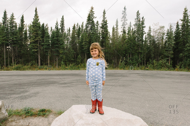 Girl standing outside on a windy day in pajamas and cowboy boots