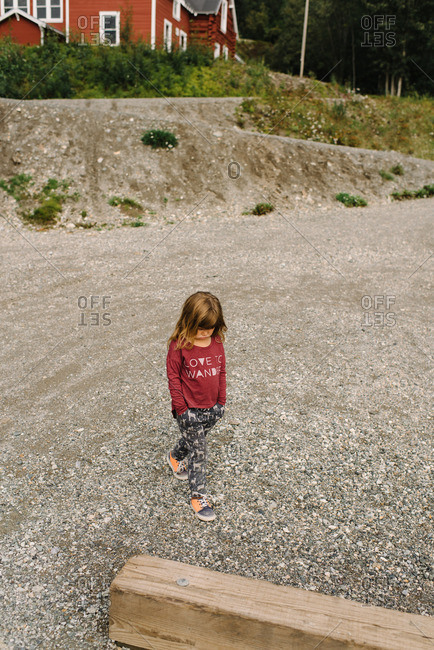 Girl walking alone outside at the Kennecott Mines National Historic Landmark in Kennecott, Alaska
