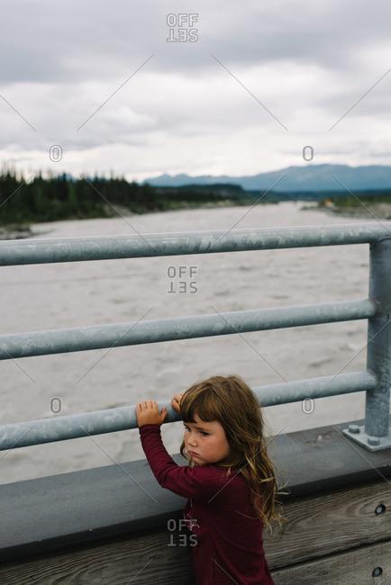 Girl standing alone outside at the Kennecott Mines National Historic Landmark in Kennecott, Alaska