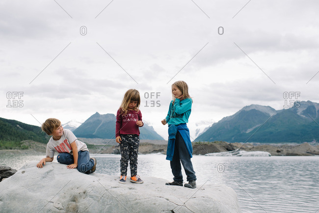 Children sitting on a rocky outcropping in the Alaskan wilderness