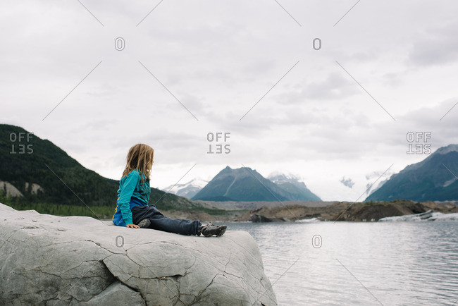 Child sitting on a rocky outcropping in the Alaskan wilderness