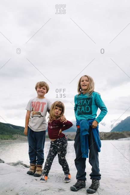 Children standing together on a rocky outcropping in the Alaskan wilderness