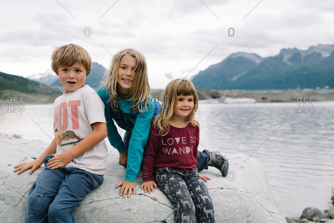 Children sitting together on a rocky outcropping in the Alaskan wilderness
