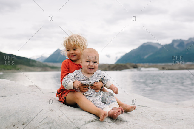 Two young children sitting together on a rocky outcropping