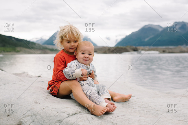 Two young children sitting together on a rocky outcropping overlooking a lake