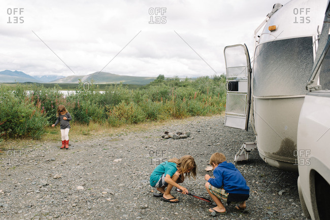 Children playing outside next to their camper trailer in Denali, Alaska