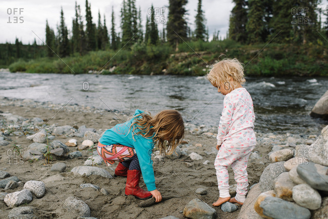 Two young girls exploring a rocky riverside