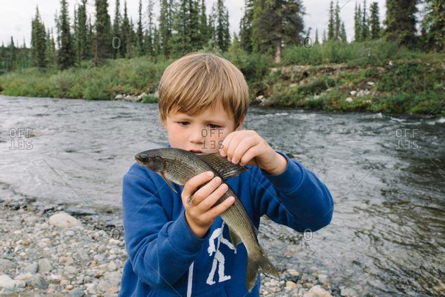 Boy holding a fish along a rocky riverside