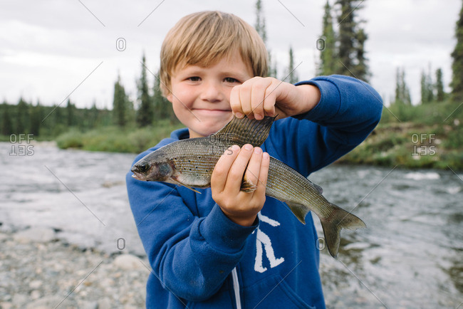 Smiling boy holding a fish along a rocky riverside