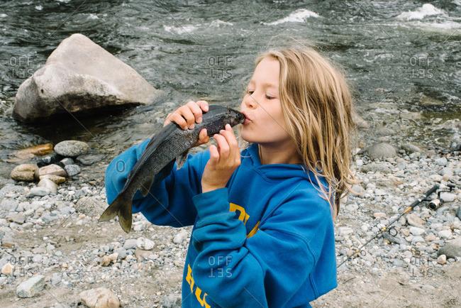 Child kissing a fish along a rocky riverside