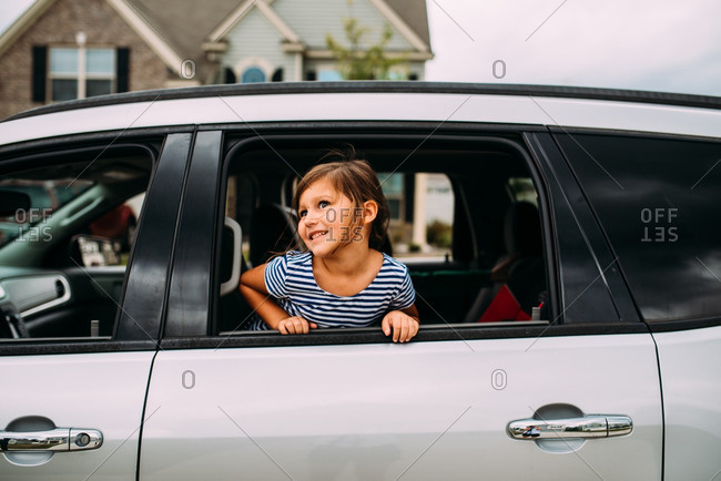 Little girl looking out window of white car