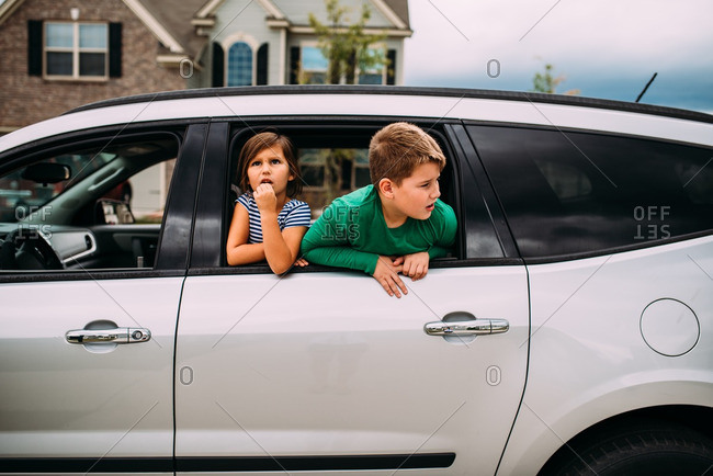 Two children looking out window of white car