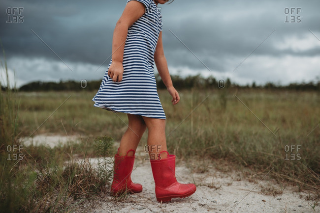 Little girl walking in a field with red rain boots