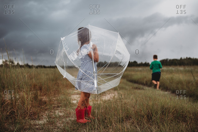 Little girl holding clear umbrella in a country field while her brother walks by