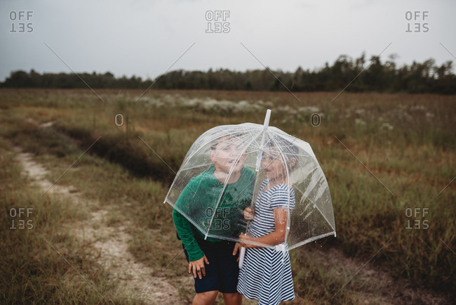 Children standing under a transparent umbrella in the rain