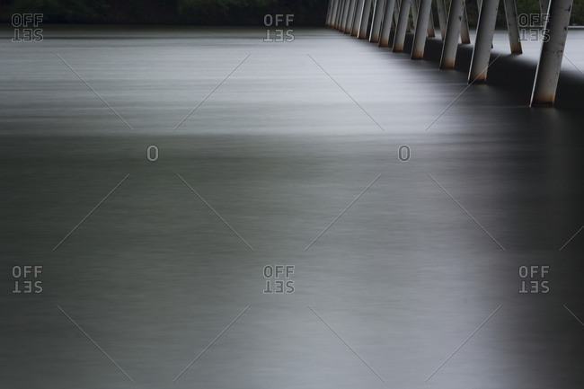 A long exposure of water on a lake with a piers supporting a pedestrian bridge