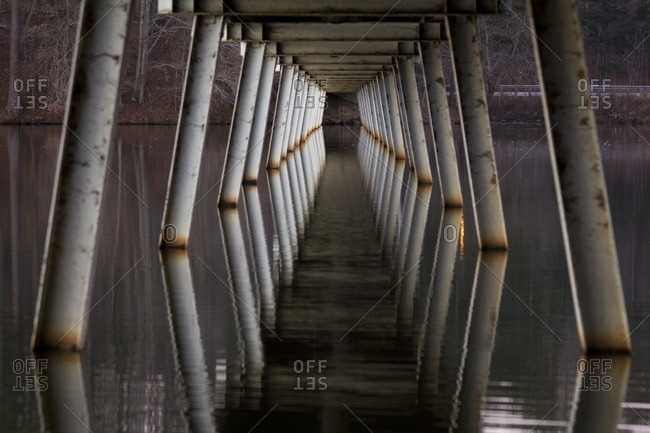 Piers supporting a pedestrian bridge with reflection in water