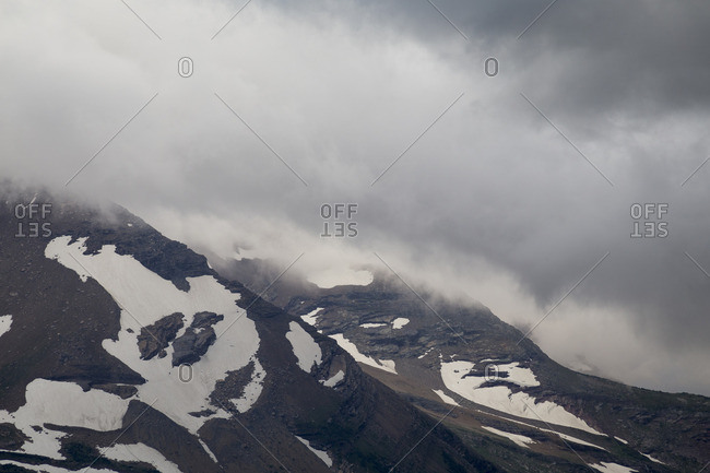 Clouds break-up near the face of a glacier covered mountain